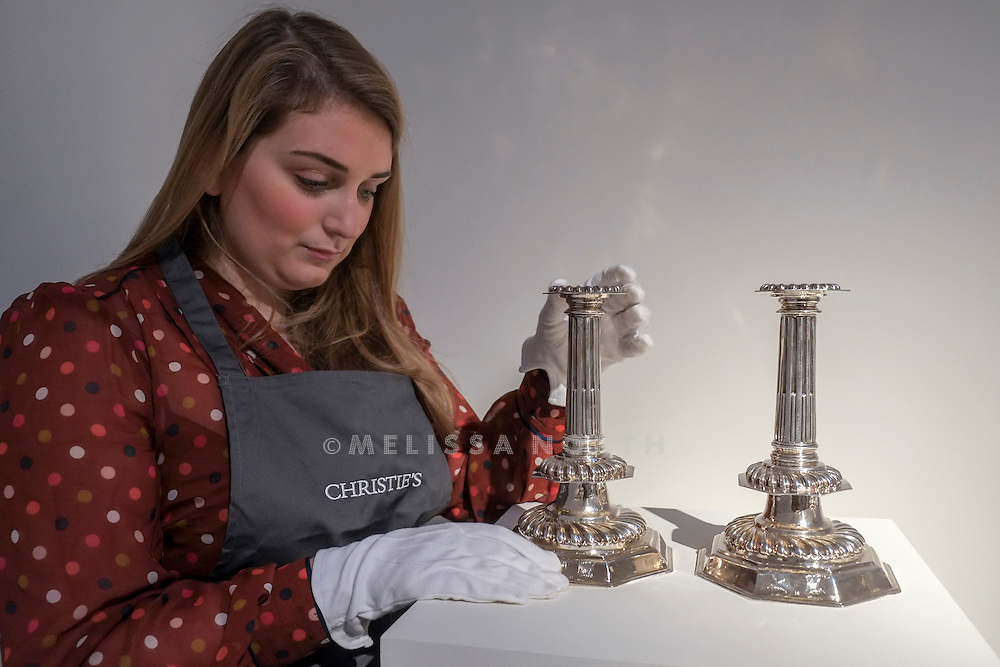 A Christie's member of staff holds one of a Pair of Large William and Mary Silver Candlesticks<br /> from the touring highlights of The Collection of Robert Hatfield Ellsworth, <br /> at Christies in King St, London, UK on Tuesday 16th December 2014. In celebration of this unparalleled collection of Asian Art, Christie's will host a series of auctions and online-only sales during New York Asian Art Week in March 2015. Photo by Melissa North. Ref B5690