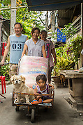 "11 JANUARY 2013 - BANGKOK, THAILAND:      A family walks home with their shopping, pet and child in a cart in the Ban Krua neighborhood in Bangkok. The Ban Krua neighborhood of Bangkok is the oldest Muslim community in Bangkok. Ban Krua was originally settled by Cham Muslims from Cambodia and Vietnam who fought on the side of the Thai King Rama I. They were given a royal grant of land east of what was then the Thai capitol at the end of the 18th century in return for their military service. The Cham Muslims were originally weavers and what is known as ""Thai Silk"" was developed by the people in Ban Krua. Several families in the neighborhood still weave in their homes.      PHOTO BY JACK KURTZ"