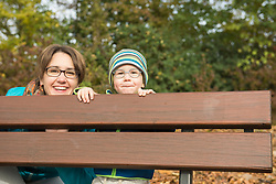 Portrait of mother and son looking from behind the backrest of bench