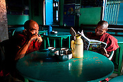 Monks drink their morning tea and read the newspaper at a café along the Chindwin River in Myanmar.