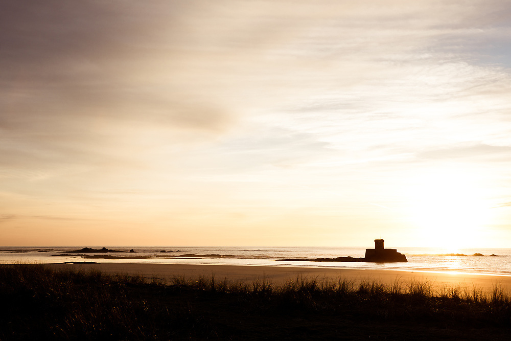 View from the sand dunes of the sun setting behind a silhouette of La Rocco Tower, a landmark and heritage site at St Ouen's Bay in Jersey, Channel Islands