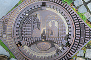 Looking down on old iron manhole cover in city of  Trondheim,  Norway