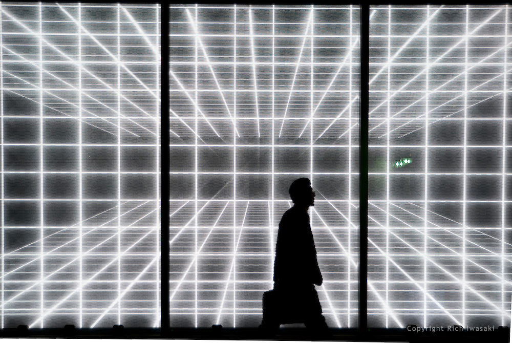 Pedestrian passes in front of electronic sign of Restir store at the Galleria,, Tokyo Midtown, Roppongi district, Tokyo, Japan