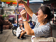 07 OCTOBER 2014 - GEORGE TOWN, PENANG, MALAYSIA: A woman releases a bird to make merit at the Goddess of Mercy shrine in central George Town (also Georgetown), the capital of the state of Penang in Malaysia. Named after Britain's King George III, George Town is located on the north-east corner of Penang Island. The inner city has a population of 720,202 and the metropolitan area known as George Town Conurbation which consists of Penang Island, Seberang Prai, Kulim and Sungai Petani has a combined population of 2,292,394, making it the second largest metropolitan area in Malaysia. The inner city of George Town is a UNESCO World Heritage Site and one of the most popular international tourist destinations in Malaysia.         PHOTO BY JACK KURTZ