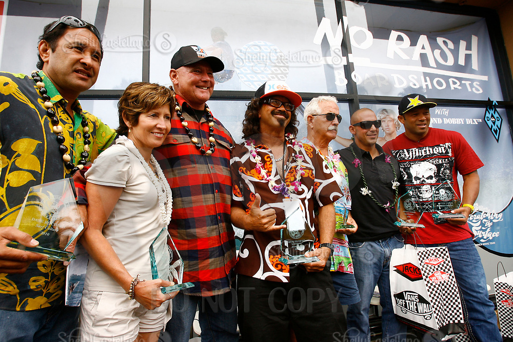 """5 August 2010: Surfing Walk of Fame ceremony at Jacks Surfboards with Rick """"rockin' fig' Fignetti local hero before the U.S. Open of Surfing at the Huntington Beach pier. Pua Rochlen, Una Baker, Ian Cairns, Rick Rockin' Fig Fignetti, Chuck Linnen, Shea Weber and Sunny Garcia are all together on stage after an induction ceremony into the Huntington Beach Walk of Fame on Main Street infront of Jacks Surf Shop. ©2010ShellyCastellano/SCPIX"""