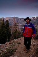 Hiker on trail in evening light over alpine mountains in Desolation Wilderness, El Dorado National Forest, California