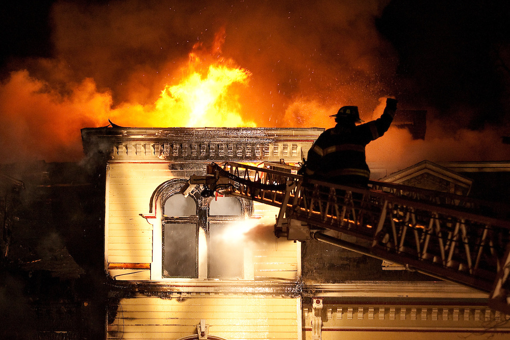 Newton, MA 02/21/2011.A Newton firefighter signals from Ladder 3 while fighting a 4 alarm structure fire at 56 Waverly Ave in Newton early Monday morning.  One occupant was transported to Newton-Wellesley Hospital and another one remained unaccounted for, officials said..Alex Jones / For The Newton TAB