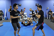 """Melvin Yeoh, South Malaysia Muay Thai Champion,  foreground with trainer. Florian Garel, Zendokai Karate Champion background with trainer. They both prepare for their fights in blue locker room<br /><br />MMA. Mixed Martial Arts """"Tigers of Asia"""" cage fighting competition. Top professional male and female fighters from across Asia, Russia, Australia, Malaysia, Japan and the Philippines come together to fight. This tournament takes place in front of a ten thousand strong crowd of supporters in Pelaing Stadium. Kuala Lumpur, Malaysia. October 2015"""