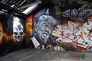 Street art mural of a grimmacing former US President Donald Trump wearing a dunces hat next to a human skull in Digbeth on 31st March 2021 in Birmingham, United Kingdom. Trump and the image of him has been the subject of much derision both during and after his presidency, and to some becoming a figure of hate, who has been heavily satirised and mocked.