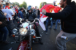 14 September 2017 - Europa League Football - Arsenal v FC Koln - A FC Koln fan waves a flag at an unamused motorbike rider stuck in the crowd - Photo: Charlotte Wilson