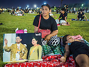 17 OCTOBER 2016 - BANGKOK, THAILAND: Mourners with a portrait of Bhumibol Adulyadej, the King of Thailand, gather on Sanam Luang, near the Grand Palace. Thai King Bhumibol Adulyadej died Oct. 13, 2016. He was 88. His death comes after a period of failing health. Bhumibol Adulyadej, was born in Cambridge, MA, on 5 December 1927. He was the ninth monarch of Thailand from the Chakri Dynasty and is also known as Rama IX. He became King on June 9, 1946 and served as King of Thailand for 70 years, 126 days. He was, at the time of his death, the world's longest-serving head of state and the longest-reigning monarch in Thai history.        PHOTO BY JACK KURTZ