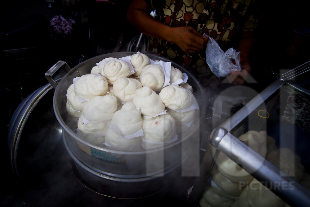 A woman selling banh bao (steamed buns) at a roadside stall in Hanoi, Vietnam