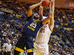 Feb 9, 2019; Morgantown, WV, USA; West Virginia Mountaineers forward Esa Ahmad (23) shoots while defended by Texas Longhorns forward Dylan Osetkowski (21) during the second half at WVU Coliseum. Mandatory Credit: Ben Queen-USA TODAY Sports