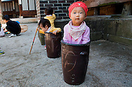 """Jung Ha-yoon, 2, appears to be stuck inside a ceramic container traditionally used to ferment Kimchi, while playing with other children at the traditional sports square during the """"Taste Korea! Korean Royal Cuisine Festival"""" held at Unhyeon Palace, also known as Unhyeongung Royal Residence, in Seoul, South Korea, on Tuesday, Oct. 1 2013. (AP Photo/Jacquelyn Martin)"""