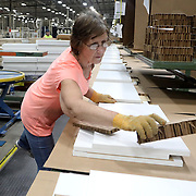 Lynn Gruber, a 19 year employee of Sauder, of Archbold, packs wooden pieces for a furniture item at Sauder Woodworking Factory in Archbold, Ohio, on Wednesday, July 25, 2018. Much of the work being done in the pictures are wooden furniture pieces for Ikea. THE BLADE/KURT STEISS