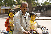 A father and his children head home after after the festival of Holi in the city of Jaipur, Rajasthan, India