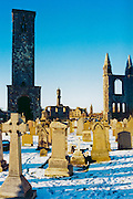 Gravestones in cemetery during snowy winter. St Andrews, Scotland <br />