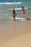 Two children (10 years old and 6 years old) playing on beach. Manly, Sydney, Australia
