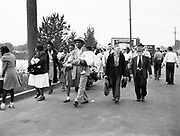 """Y-480530-02.  """"A man in a suit and hat carries a baby girl. His wife walks just behind him to his right. They are David Kizer, 32, and Ruth Kizer, 19. He carries their daughter, Barbara, 11 days shy of 1 year. They and others walk with a determined stride on North Denver Avenue."""" (excerpt of caption published in the Oregonian, May 24, 1998, page M2.) May 30, 1948."""