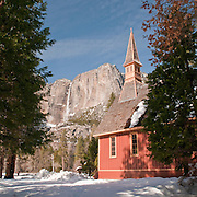 Winter in Yosemite with this image of Yosemite Valley Chapel in the wintry foreground of Yosemite Falls.