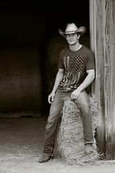 hot cowboy sitting on a hay bale  in a barn