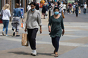 Shoppers pass through the town centre, some choosing to wear face coverings outside, on 14th July 2021 in Windsor, United Kingdom. The UK government announced on 12th July that England will move to the final stage of easing Covid-19 restrictions on 19th July, with almost all legal restrictions on social contact removed, but they also advised the public to exercise caution given that the current wave driven by the Delta variant is not expected to peak until mid-August.