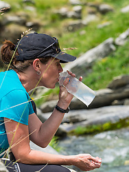 Woman hiker drinking water, Gavarnie, France