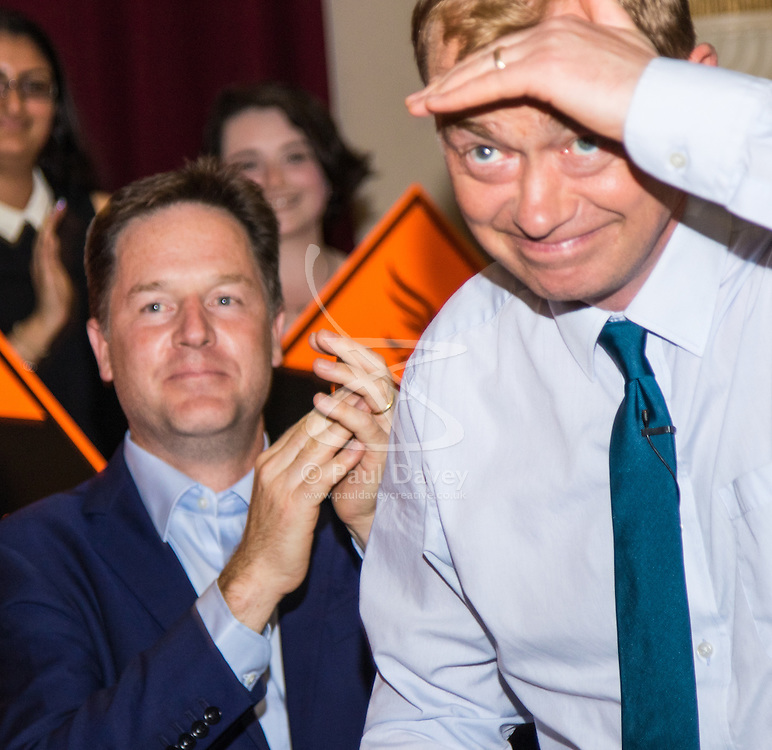 Islington Assembly Hall, London, July 16th 2015. The Liberal Democrats announce their new leader Tim Farron MP who was elected by party members in a vote against Norman Lamb MP. PICTURED: Out with the old, in with the new - former Liberal Democrat Leader Nick Clegg applaudes as Tim Farron takes to the podium to a burst of camera flashes.