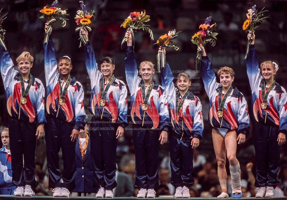 ATLANTA - JULY 23:   The United States Women's Gymnastics Team (L-R) of Amanda Borden, Dominique Dawes, Amy Chow, Jaycie Phelps, Dominique Moceanu, Kerri Strug, and Shannon Miller salutes the crowd after receiving their gold medals in the Team competition of the 1996 Summer Olympic Games held on July 23, 1996 in the Georgia Dome in Atlanta, Georgia.  The USA Women's team was nicknamed the Magnificent Seven.  (Photo by David Madison/Getty Images)