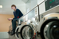 Young woman listening music on top of washing machine, smiling