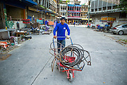"""11 DECEMBER 2012 - BANGKOK, THAILAND: A worker pushes a cart of cables used in demolition through the empty buildings at """"Washington Square"""" a notorious entertainment district off Sukhumvit Soi 22 in Bangkok. Demolition workers on many projects in Thailand live on their job site tearing down the building and recycling what can recycled as they do so until the site is no longer inhabitable. They sleep on the floors in the buildings or sometimes in tents, cooking on gas or charcoal stoves working from morning till dark. Sometimes families live and work together, other times just men. Washington Square was one of Bangkok's oldest red light districts. It was closed early 2012 and is being torn down to make way for redevelopment.    PHOTO BY JACK KURTZ"""