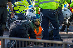 © Licensed to London News Pictures.  04/10/2021. London, UK. An activist from Insulate Britain is being unglued from the road by a police officer as eco-protesters have blocked the A12 Blackwell Tunnel Northern Approach in east London. Photo credit: Marcin Nowak/LNP