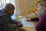 A young African boy practices writing with a female volunteer in a classroom in Zonnebloem School, Cape Town, South Africa.  The volunteer uses a variety of literacy tools to help the children learn to read and write, these include the assisted reading books, flash cards and alphabet posters which can be seen in the picture.  The volunteer is from the Shine Centre organisation which aims to address the high illiteracy rate in South Africa by improving literacy levels among children in schools and disadvantaged communities.