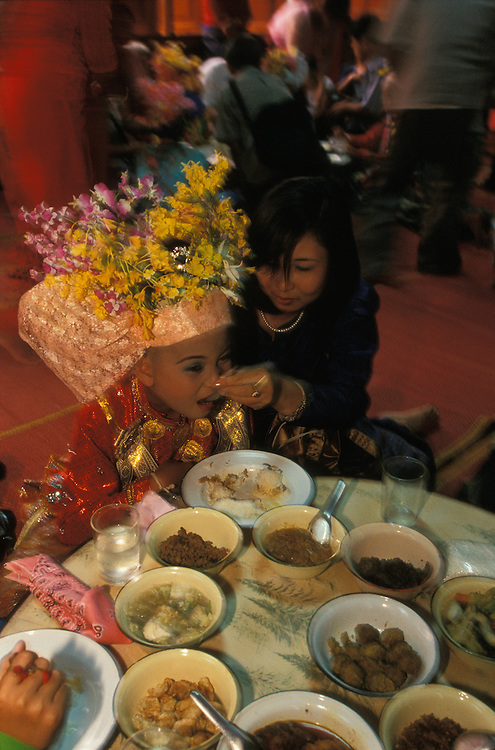 Mother feeds her son with twelve different dishes in the temple as part of the Poy Sang Long, the ordination of novice monks, Mae Hong Son, Thailand.