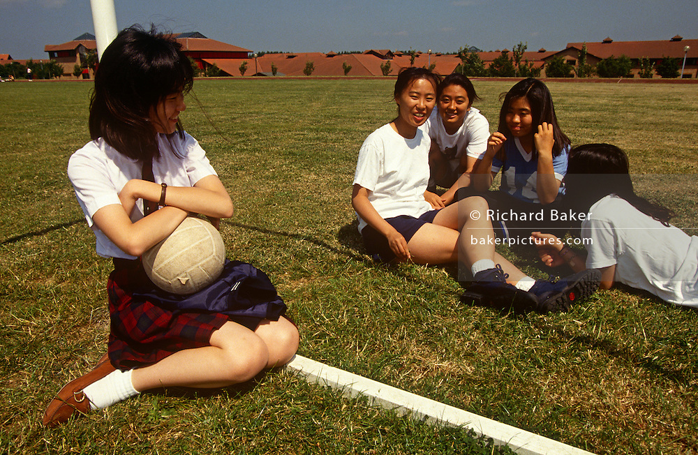 Teenage girl students sit on the sports field during a lunchtime break at the Gyosei International Japanese School, a boarding school for Japanese ex-pats opened in 1987 in Willen Park, Milton Keynes, England. Giggling and smiling in their happy environment, the young women enjoy life in the UK, the children of skilled parents working in England. The Gyosei independent private school was the first of its type established in the country and shows the importance of Milton Keynes as a focus for Japanese investment..