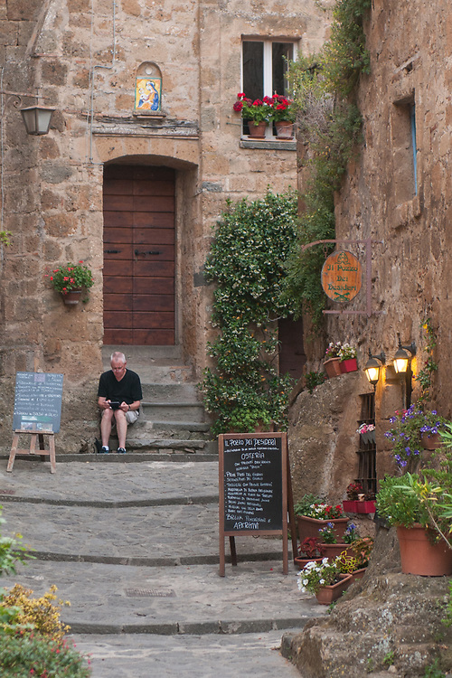 """A tourist relax on some stairs of the village of Civita di Bagnoregio.<br /> Civita di Bagnoregio is a town in the Province of Viterbo in central Italy, a suburb of the comune of Bagnoregio, 1 kilometre (0.6 mi) east from it. It is about 120 kilometres (75 mi) north of Rome. Civita was founded by Etruscans more than 2,500 years ago. Bagnoregio continues as a small but prosperous town, while Civita became known in Italian as La città che muore (""""The Dying Town""""). Civita has only recently been experiencing a tourist revival. The population today varies from about 7 people in winter to more than 100 in summer.The town was placed on the World Monuments Fund's 2006 Watch List of the 100 Most Endangered Sites, because of threats it faces from erosion and unregulated tourism."""