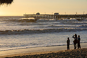 People Watching the Big Waves on the Beach at Sunset