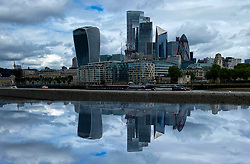 © Licensed to London News Pictures. 31/07/2021. London, UK. A reflection of London's financial district in a puddle of rain water. Puddle caused by heavy rain fall in the capital. Photo credit: Dinendra Haria/LNP