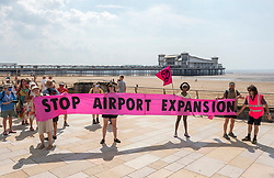 """© Licensed to London News Pictures;22/07/2021; Weston-super-Mare, UK. Campaigners against the expansion of Bristol Airport stage a protest with a banner saying """"Stop Airport Expansion"""" through Weston-super-Mare Town Centre and along the beach promenade on the third day of the planning appeal inquiry at Weston's Town Hall into the proposal to expand the airport. North Somerset councillors rejected the expansion proposals in 2020 and now a planning appeal has been launched by Bristol Airport. The expansion of Bristol Airport would allow an extra 23,800 flights a year to new destinations. Campaigners including Bristol Airport Action Network (BAAN) and Extinction Rebellion say that science shows airports should not be expanded due to the effects of climate change which are extreme and damaging for our planet, and for children. They also say for an airport expansion to be approved in the same year when the UK is hosting the COP26 climate summit would be a national and international disgrace. Photo credit: Simon Chapman/LNP."""