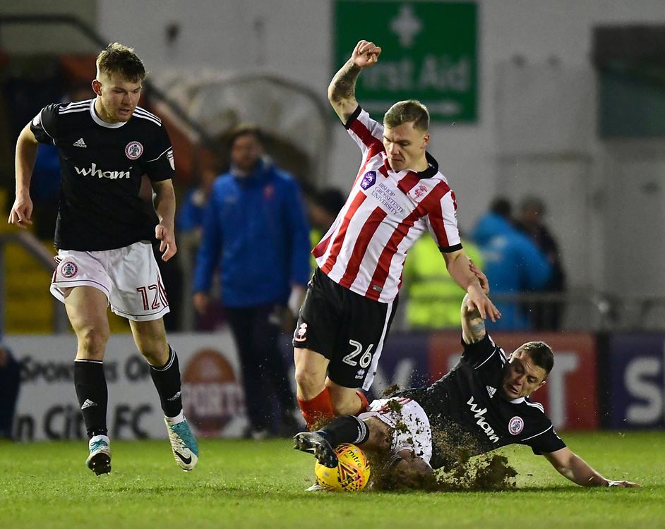 Lincoln City's Harry Anderson is tackled by Accrington Stanley's Scott Brown<br /> <br /> Photographer Chris Vaughan/CameraSport<br /> <br /> The EFL Sky Bet League Two - Lincoln City v Accrington Stanley - Saturday 16th December 2017 - Sincil Bank - Lincoln<br /> <br /> World Copyright © 2017 CameraSport. All rights reserved. 43 Linden Ave. Countesthorpe. Leicester. England. LE8 5PG - Tel: +44 (0) 116 277 4147 - admin@camerasport.com - www.camerasport.com