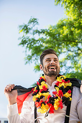 Excited male soccer fan watching soccer, Munich, Bavaria, Germany