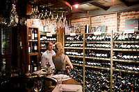 The wine steward at Azafrán helps a customer pick a bottle of wine for dinner in Mendoza, Argentina. The restaurant allows customers to purchase a bottle from it's cellar.