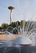 """A flock of geese flies over the International Fountain below the Space Needle. The International Fountain was built for the 1962 World's Fair at Seattle Center, Washington, USA, as a modernist water sculpture. With over 20 spouts, the musical fountain goes through programmed cycles of shooting water patterns, accompanied by recorded world music. The music is changed every month, and chosen to coordinate with the water patterns. The Space Needle (605 feet tall) annually hosts more than 1 million visitors, making it the number one tourist attraction in the Pacific Northwest. When the Space Needle was built in 1962 for the World's Fair, it was the tallest building west of the Mississippi River. The entire Space Needle saucer does not rotate, only a 14-foot ring next tthe windows rotates on the SkyCity restaurant level. The 100 foot, or SkyLine, level was built in 1982. The original name of the Space Needle was """"The Space Cage."""" The original name of the restaurant was """"Eye of the Needle.""""  Published in """"Light Travel: Photography on the Go"""" book by Tom Dempsey 2009, 2010."""