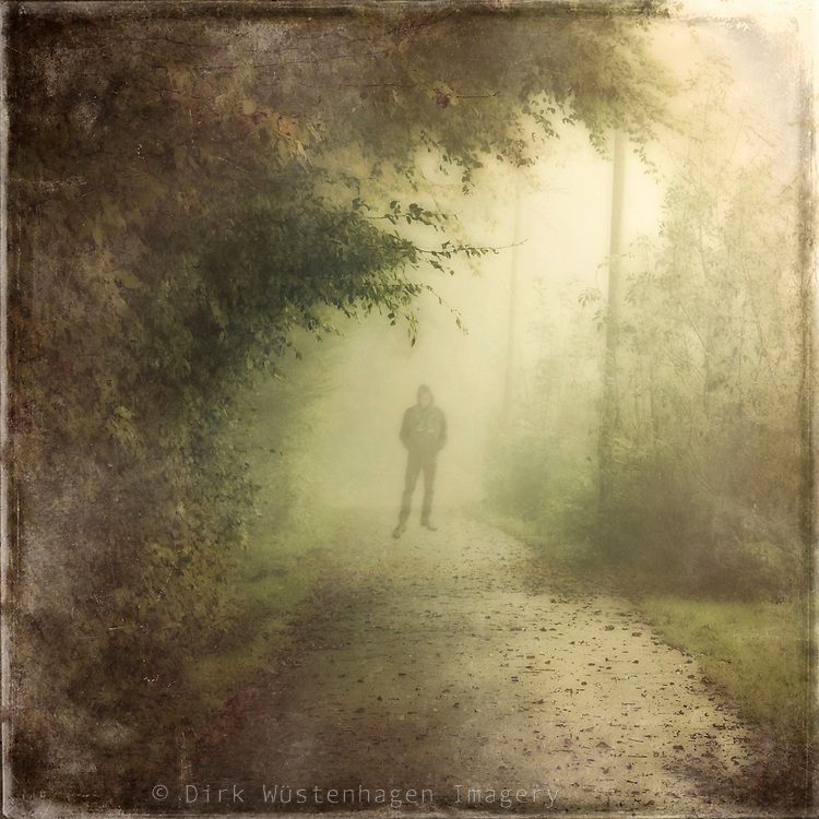 Man standing on a country road in the mist - textured photograph