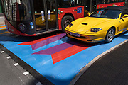 A London bus and a yellow Ferrari drive over the multi-coloured markings of a crossing at Lower Regent Street, on 16th July 2021, in London, England.