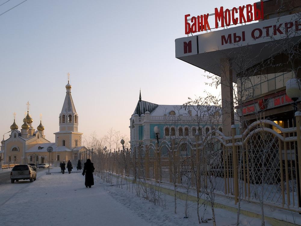 """Passanten vor einer russisch orthodoxen Kirche in der Innenstadt von Jakutsk im Kontrast zur Bankfiliale der """"Bank of Moscow"""". Jakutsk wurde 1632 gegruendet und feierte 2007 sein 375 jaehriges Bestehen. Jakutsk ist im Winter eine der kaeltesten Grossstaedte weltweit mit durchschnittlichen Winter Temperaturen von -40.9 Grad Celsius. Die Stadt ist nicht weit entfernt von Oimjakon, dem Kaeltepol der bewohnten Gebiete der Erde.<br /> <br /> Passersby infront of a Russian Orthodox church in the city center of Yakutsk - on the ride side the """"Bank of Moscow"""" office. Yakutsk was founded in 1632 and celebrated 2007 the 375th anniversary - billboard announcing the celebration. Yakutsk is a city in the Russian Far East, located about 4 degrees (450 km) below the Arctic Circle. It is the capital of the Sakha (Yakutia) Republic (formerly the Yakut Autonomous Soviet Socialist Republic), Russia and a major port on the Lena River. Yakutsk is one of the coldest cities on earth, with winter temperatures averaging -40.9 degrees Celsius."""