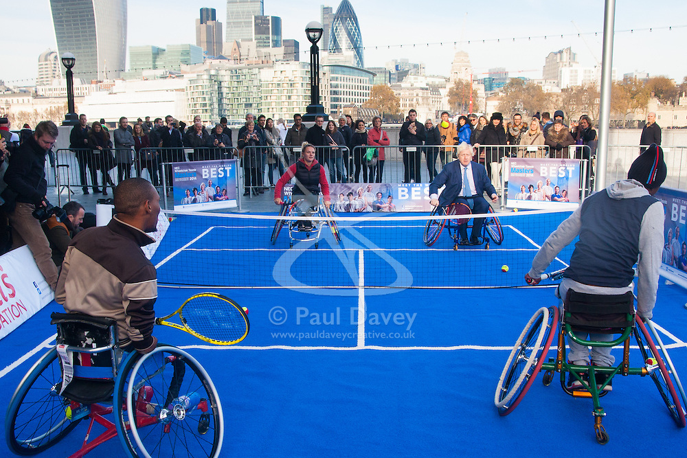 City Hall, London, November 24th 2014. Mayor Boris Johnsonwelcomes the world's best wheelchair tennis players with a game of mini tennis outside City Hall. The players are in London to compete in the NEC Wheelchair Tennis Masters 2014, being held at the Lee Valley Hockey and Tennis Centre, being held from 26 - 30 November. PICTURED: Mayor Boris Johnson plays a game of sudden death tennis with wheelchair tennis competitors Lucas Sithole, left, Jordanne Whiley, second left, and KgothatsoMontjane, right, outside City  Hall.