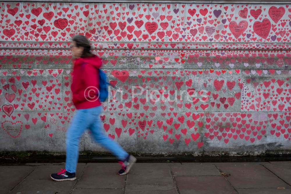 A woman wearing a red jacket walks past the National Covid memorial wall, a sea of red love hearts remembering all those who have died due to the COVID-19 pandemic on the 25th of May 2021 on the south bank in London, United Kingdom. Over 150,000 people have lost their lives in the United Kingdom due to the pandemic, the wall is a space for them to be remembered.