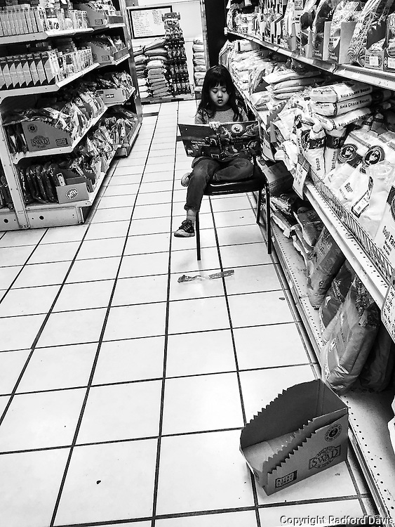 Young girl reads in the aisle of the supermarket