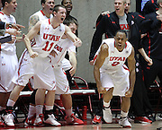 Utah guard Chris Hines, right, celebrates with Alex Mortensen (11) and others on the bench after scoring a go ahead, three-point basket late in the second half of an NCAA college basketball game against Stanford, Saturday, Feb. 25, 2012, in Salt Lake City. Utah beat Stanford 58-57. (AP Photo/Colin E Braley).